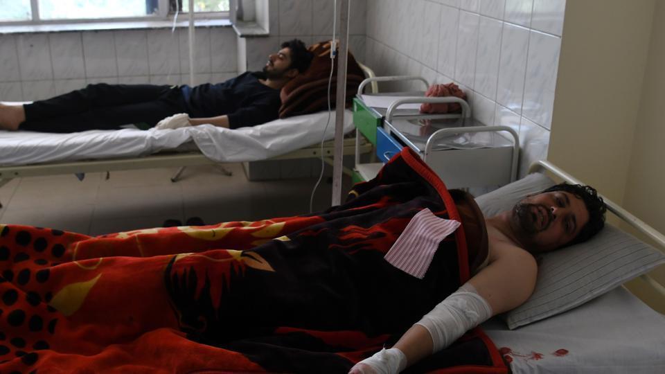 Afghan men rest in a hospital after being injured in a car bomb attack in Kabul. (SHAH MARAI / AFP)
