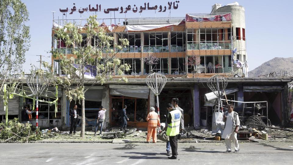 Municipality workers cleans up in front of a wedding hall at the site of a suicide attack in Kabul. (Massoud Hossaini / AP)