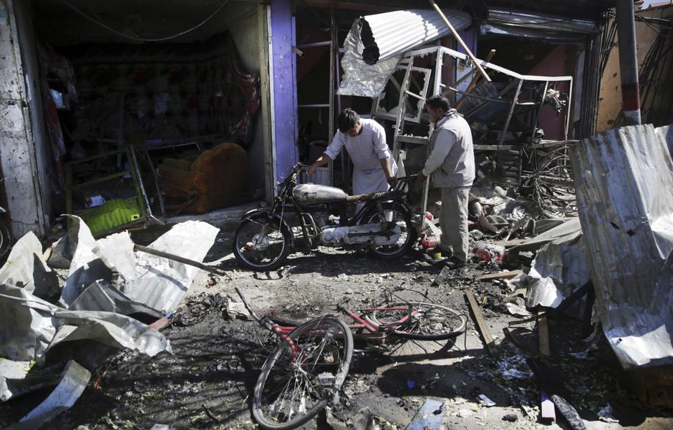 Men look at the remains of their properties at the site of a suicide attack in Kabul, Afghanistan, Monday, July 24, 2017. The Taliban have killed at least 24 people and wounded dozens more in a suicide bomb attack against a bus carrying government employees in the Afghan capital, Kabul. (Massoud Hossaini / AP)