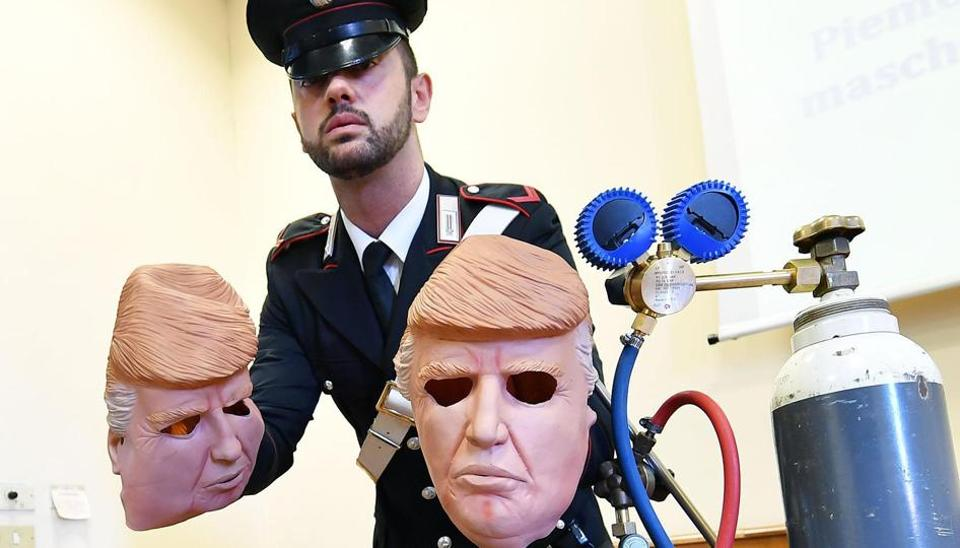 An Italian Carabinieri police officer show masks of US President Donald Trump used by two arrested robbers, Vittorio and Ivan Lafore', during a press conference held in Turin, Italy.