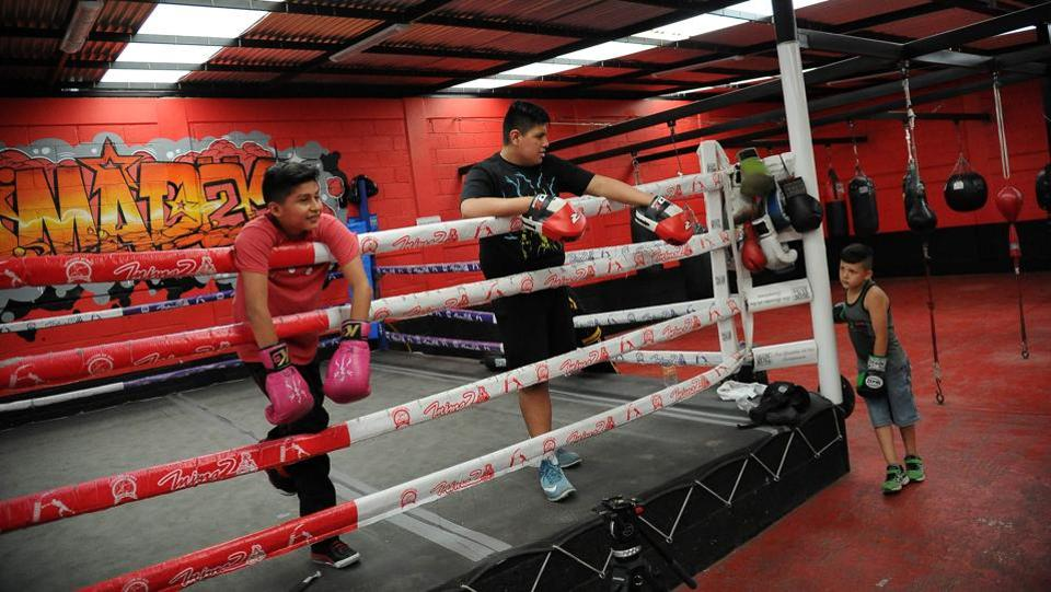 Two boys take a break in the ring during a training session at a popular gym in the outskirts of Mexico City. (Bernardo Montoya / AFP)