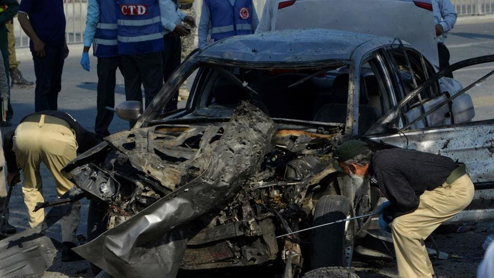 Pakistani security officials inspect a destroyed vehicle after suicide bombing in Lahore on July 24, 2017. The explosion killed 26 people and injured nearly 60 more in the eastern Pakistani city. The Pakistani Taliban claimed responsibility for the attack.