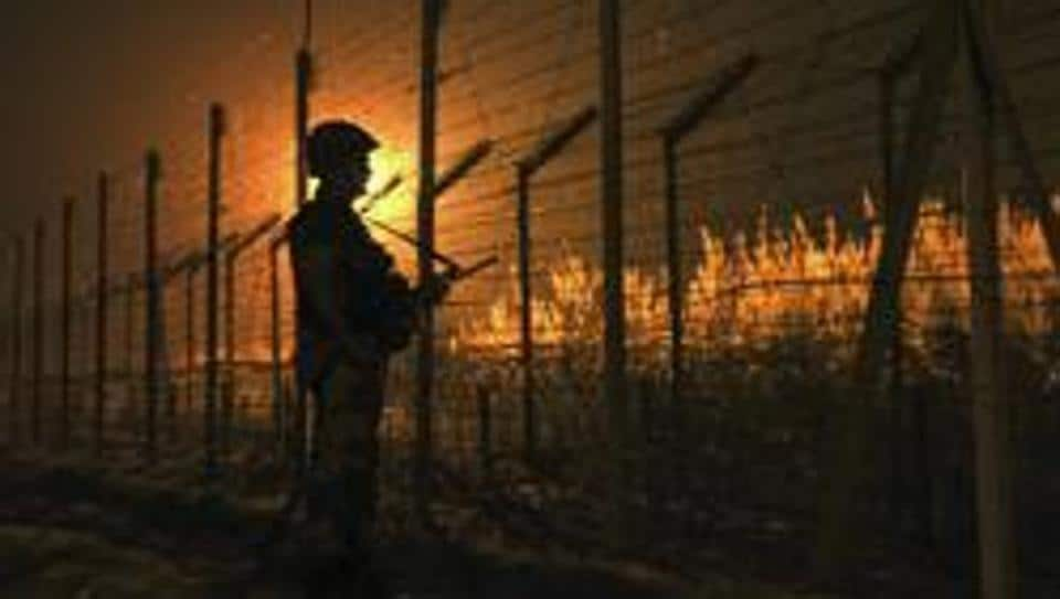 A soldier stands guard near the fence at the India-Pakistan International Border.