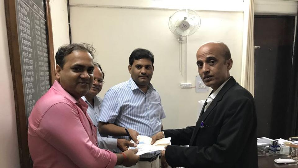 The lawyer for the Amrapali group hands over the DD of the pending amount to Dadri tehsildar PL Maurya (right), on Tuesday.