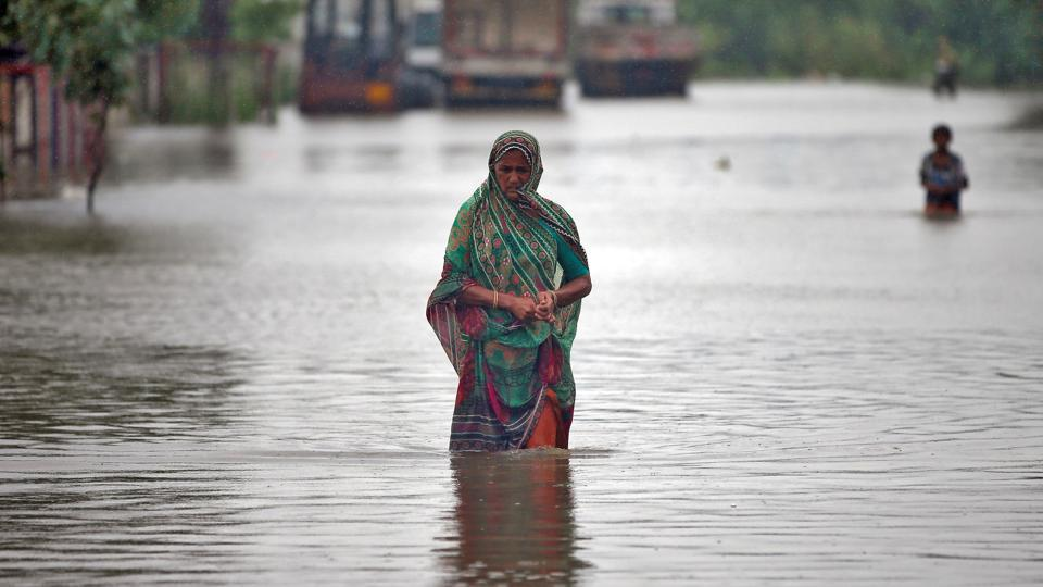 A woman walks through a flooded street in Ahmedabad, India. Incessant rain has thrown normal life out of gear in many parts Gujarat and several other parts of India.  In Gujarat, 1,526 people in Banaskantha district, about 500 in Patan district, and over 200 at Kalol in Gandhinagar district have been shifted after floods to safer places. (Amit Dave / REUTERS)