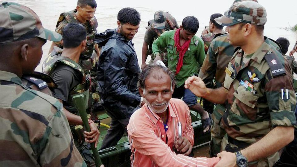 Army personnel rescue villagers,  stuck in the flooded villages due to heavy downpour at Surendranagar district, in Gujarat. (PTI)