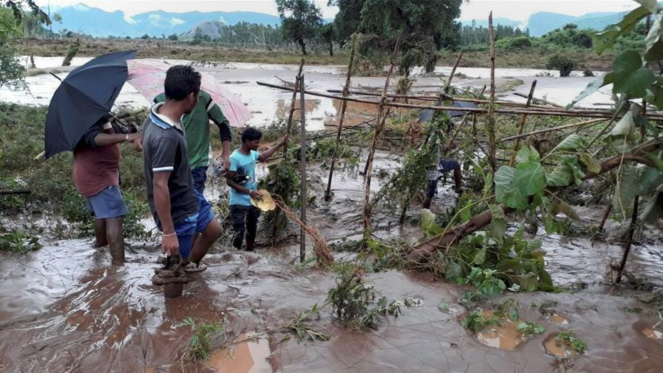 Rayagada: Volunteers try to check the water of river Nagabali during flash flood in Rayagada district, Odisha on Monday. PTI Photo(PTI7_17_2017_000171A)