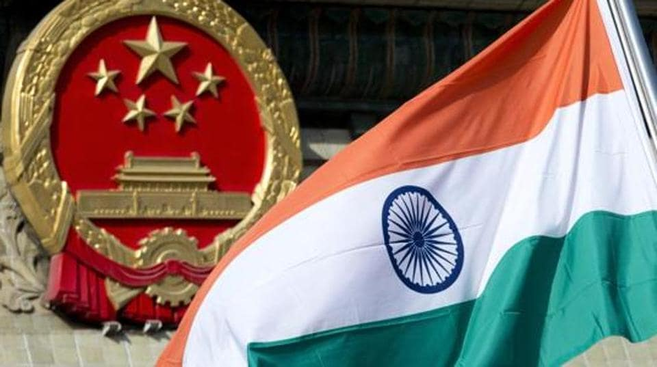 An Indian national flag is flown next to the Chinese national emblem during a welcome ceremony for visiting Indian officials outside the Great Hall of the People in Beijing. India says it is ready to hold talks with China with both sides pulling back their forces to end a standoff along a disputed territory high in the Himalayan mountains.
