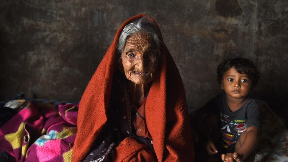 Bachiben Katia,105 year old, looks on as the family takes refuge in a railway compartment of a goods train after floods. (SAM PANTHAKY / AFP)