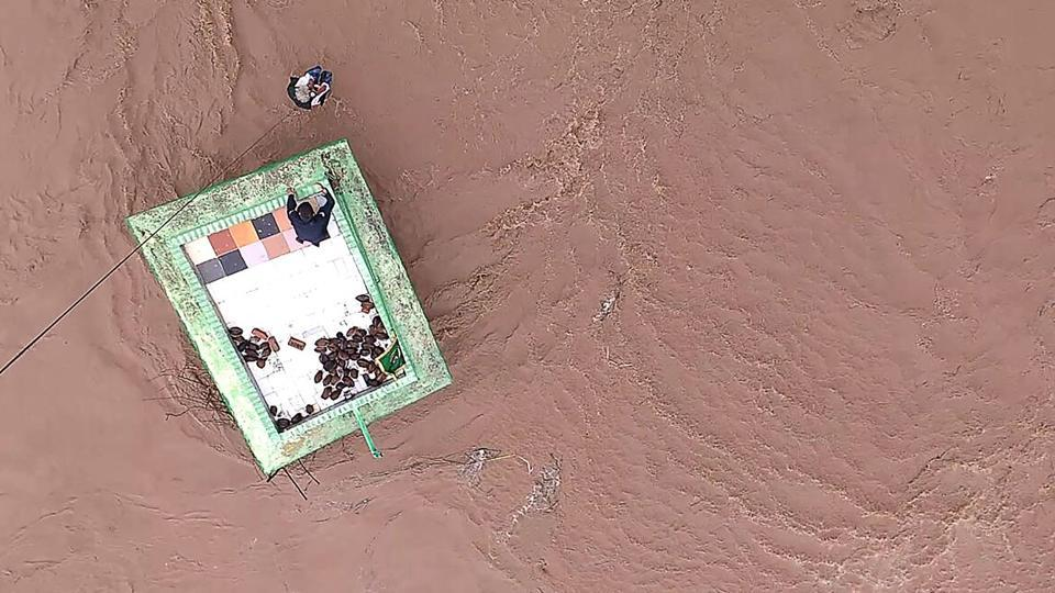 An Indian Air Force (IAF) officer after being lowered from a helicopter to help local residents taking shelter atop a Dargah (Muslim Shrine) surrounded by flood waters at Untadi village of Limdi Taluka, some 100 kms from Ahmedabad.  (AFP)