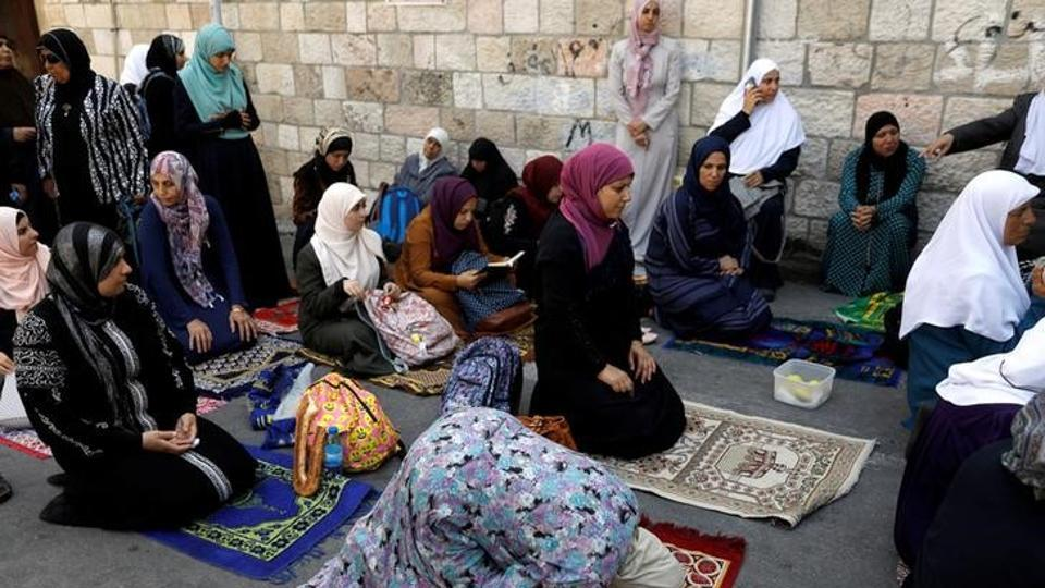Palestinian women pray outside the compound known to Muslims as Noble Sanctuary and to Jews as Temple Mount at morning after Israel removed the new security measures there, in Jerusalem's Old City July 25, 2017.