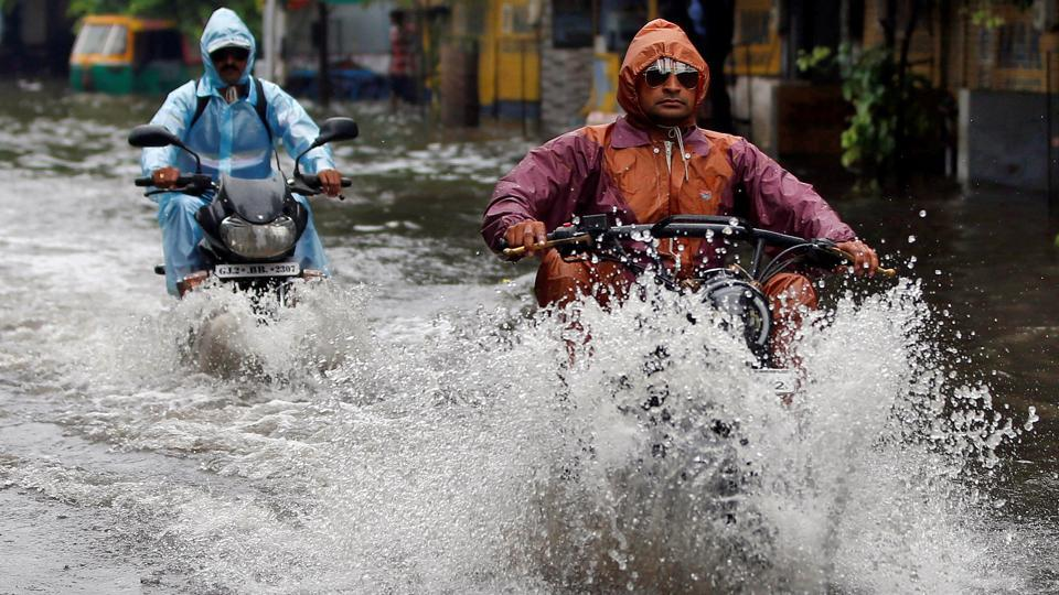 People drive through a flooded road after heavy rains in Ahmedabad. (Amit Dave / REUTERS)