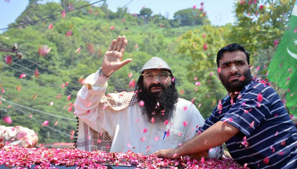 Syed Salahuddin (left), Hizbul Mujahideen chief, is showered with flower petals as he arrives to speak at a news conference in Muzaffarabad, Pakistan on July 1.