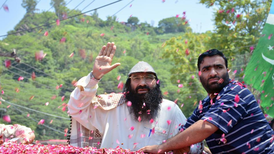 Syed Salahuddin (L), supreme commander of Hizbul Mujahideen, is showered with flower petals as he arrives to speak at a news conference in Muzaffarabad, Pakistan on July 1.