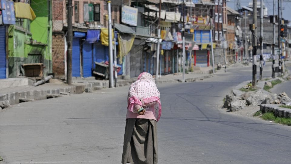 A woman walks on a deserted street in downtown Srinagar on Tuesday. Normal life was hit in the old parts of the city following Hurriyat's shutdown call and authorities restricting movement of the people.
