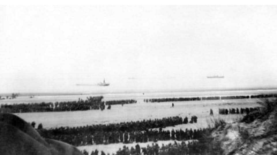 Soldiers stranded at the Dunkirk beach in 1940 (top), and the same image captured in Christopher Nolan's movie (bottom).