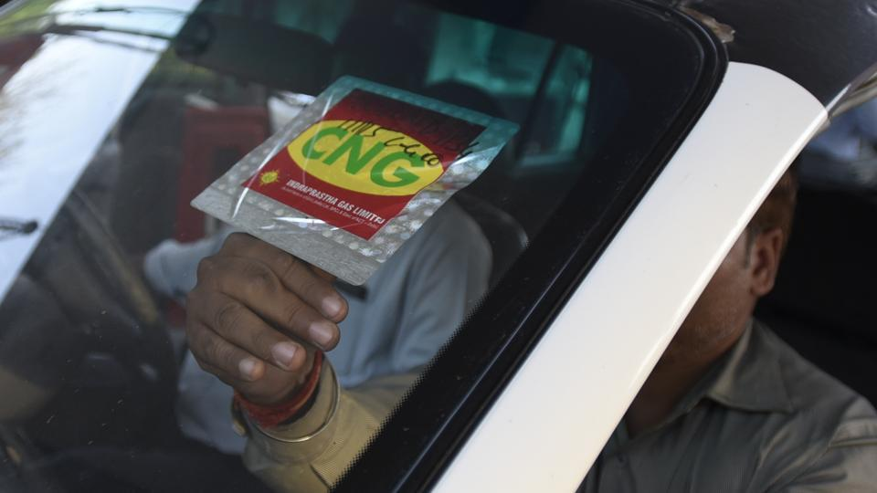 A CNG station staffer puts a sticker after on  a car after verifications.