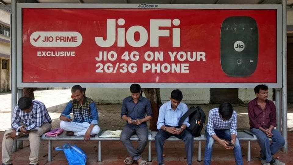 Commuters use their mobile phones as they wait at a bus stop with an advertisement of Reliance Jio.