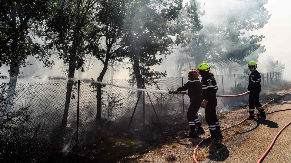 French firefighters attempt to extinguish a fire burning in Artigues, as part of a blaze that has consumed swathes of land in southeastern France for a second day in a row.  (Anne-Christine POUJOULAT / AFP)