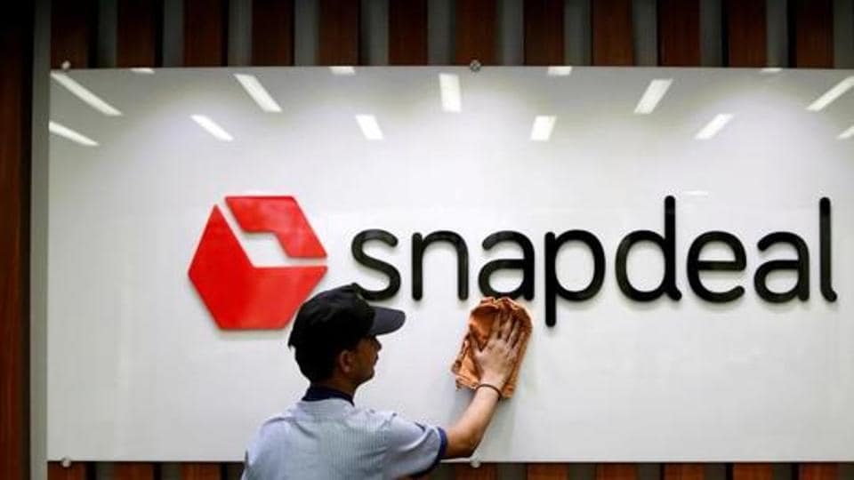 An employee cleans a Snapdeal logo at its headquarters in Gurugram.