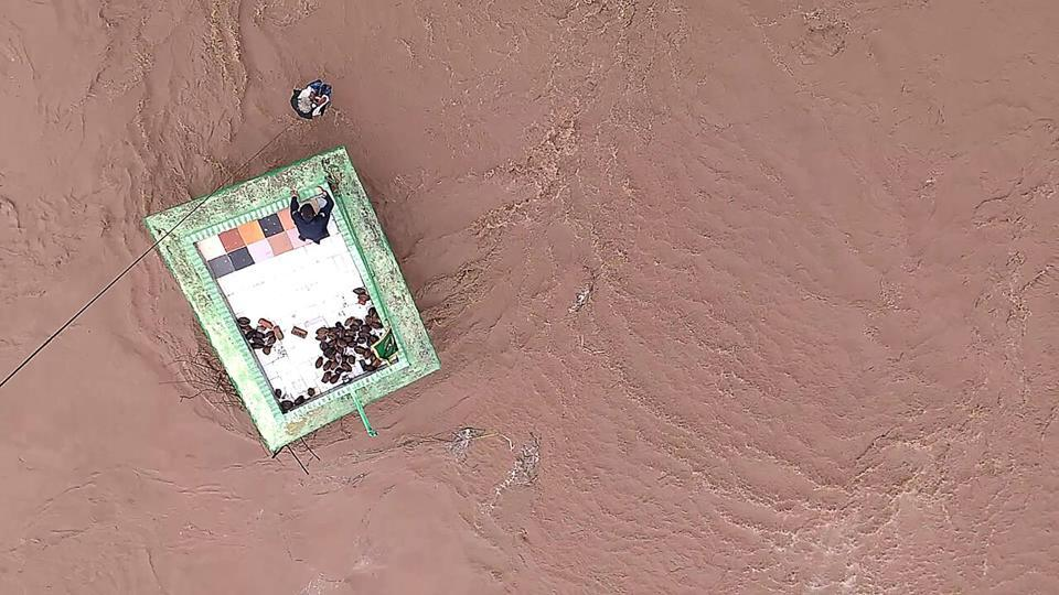 This official handout photograph shows an Indian Air Force (IAF) personnel after being lowered from an helicopter to help residents taking shelter atop a dargah  surrounded by flood waters in Gujarat.
