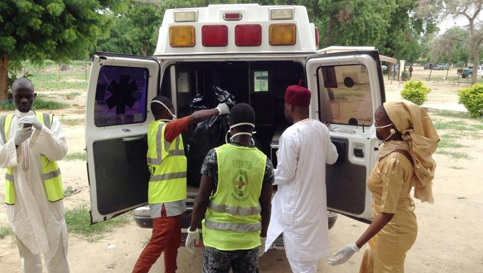 Rescue workers load the body of a victim into an ambulance following a suicide attack at the University, in Maiduguri, Nigeria, Monday, July. 24, 2017. Female suicide bombers attacked two camps for displaced people in northeastern Nigeria's main city, leaving many dead and injured.