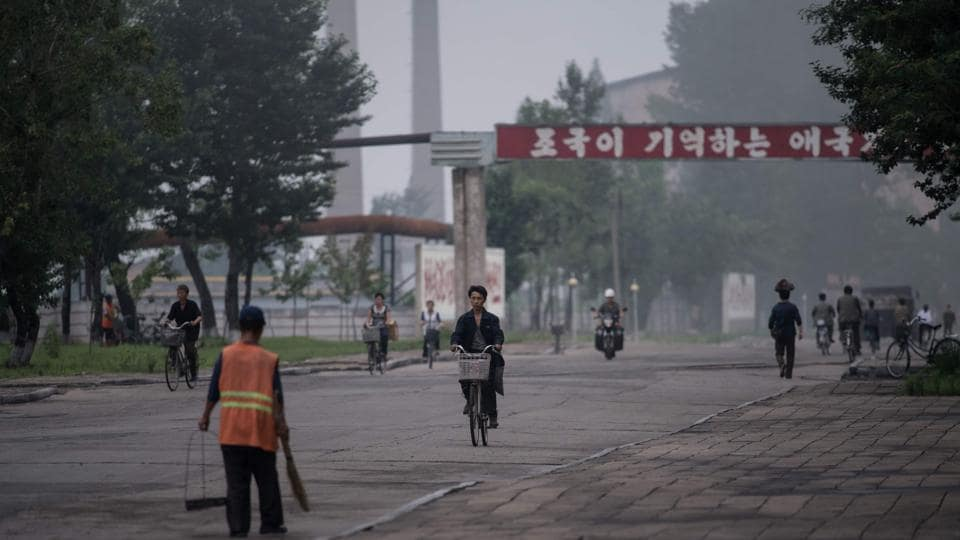 A photo taken on July 22, 2017 shows workers passing along a road at the Chollima Steel Complex, south-west of Pyongyang.
