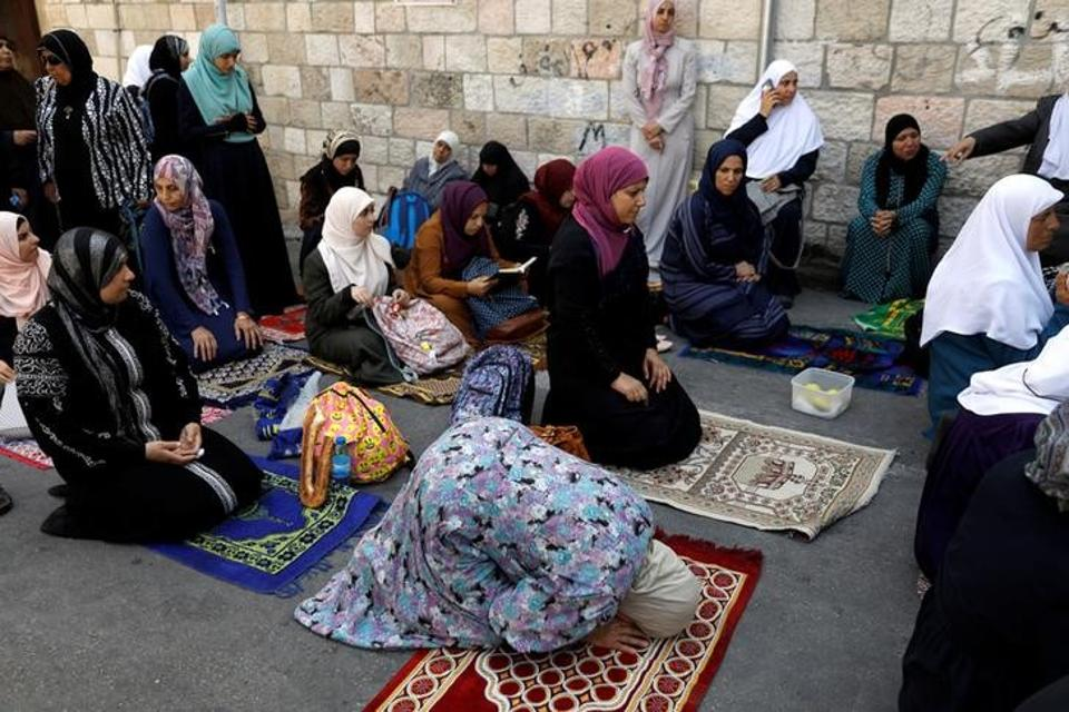 Palestinian women pray outside the al-Aqsa compound in Jerusalem on July 25, 2017.