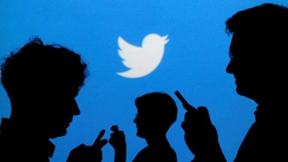 People holding mobile phones are silhouetted against a backdrop projected with the Twitter logo in this illustration picture taken September 27, 2013.