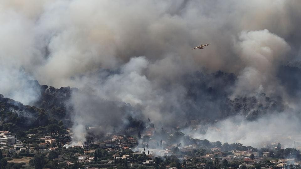 A fire fighting Canadair aircraft flies to drop water over a fire near Carros. (Valery HACHE/ AFP)