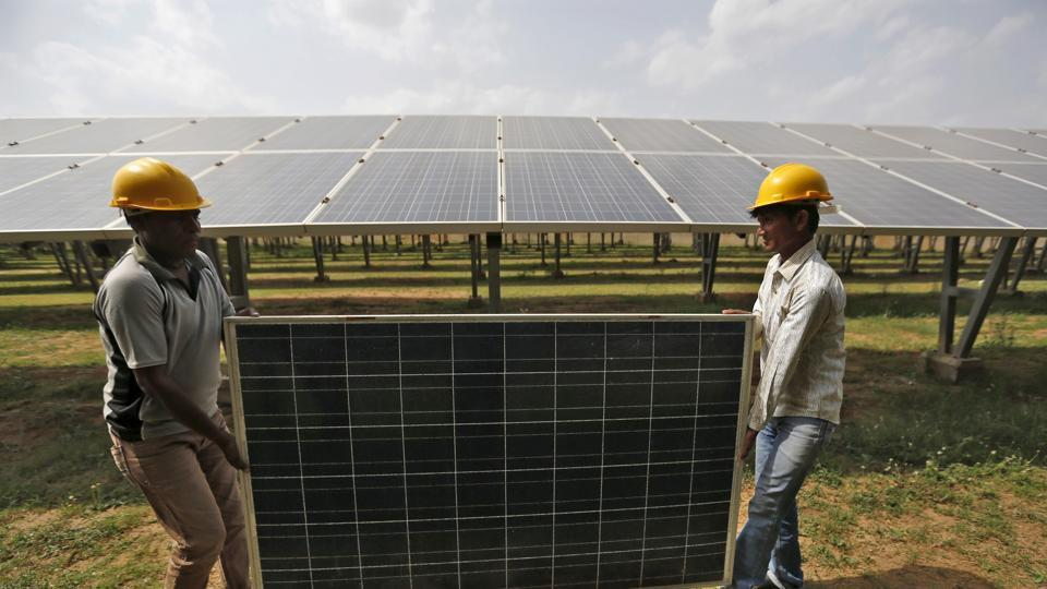Workers carry a damaged photovoltaic panel inside a solar power plant in Gujarat. India is launching an anti-dumping investigation over photovoltaic cells imported from China.