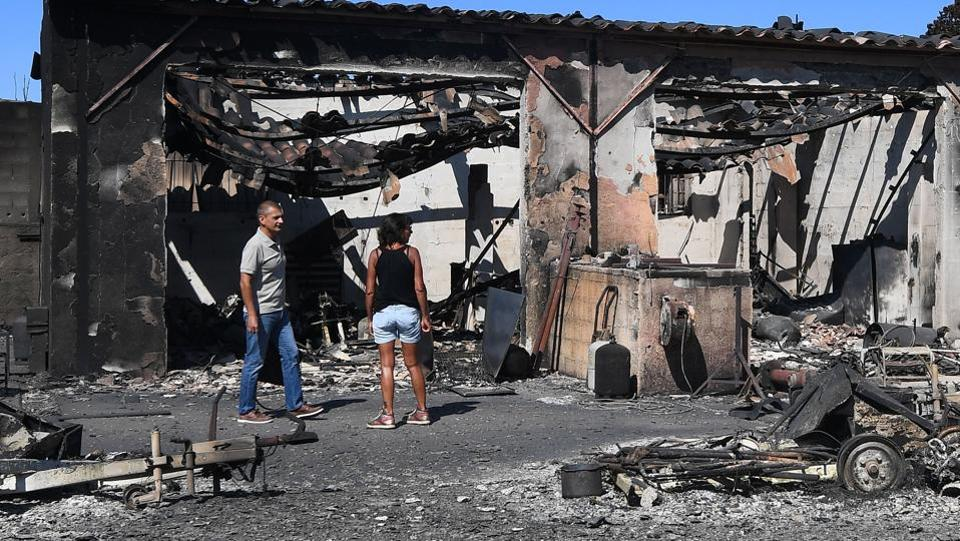 A man and woman inspect the damage as they stand next to a burnt out house following a fire in Bormes-les-Mimosas, southeastern France. Six more of the planes have been ordered by the French government while extra firefighters have been drafted in from the north of the country. (Anne-Christine / AFP)