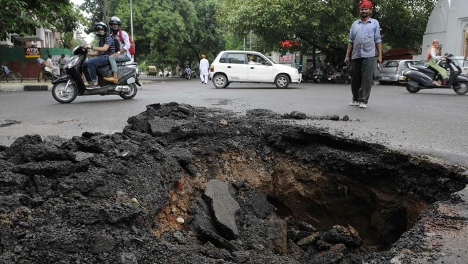 A part of road caved in sector 46, Chandigarh, after heavy rains lashed the region on Thursday.  (Keshav Singh/HT Photo)