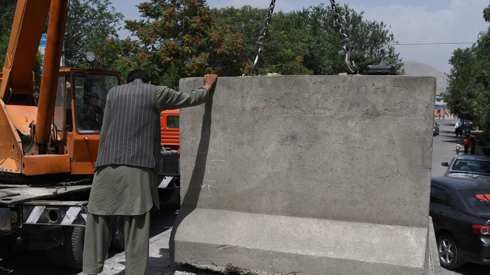 An Afghan government worker removes blast walls in Kabul. The blast walls that cut through Kabul like ramparts are being pulled down, part of a counter-intuitive makeover by local officials who argue the move will give the city's war-weary residents a psychological boost.
