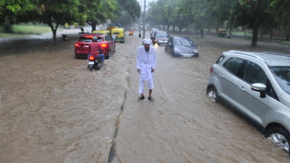 A man stands on a divider road at sector 17-18 road after heavy rains led to water logging in Chandigarh on Thursday. (Ravi Kumar/HT Photo)