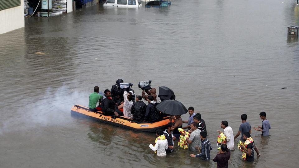 Voluteers carry out relief works in a flooded locality after heavy rains in Ahmedabad on Thursday.