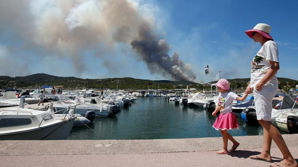 A woman and her daughter walk near leisure boats as a plume of smoke from burning fires fills the sky in Bormes-les-Mimosas, in the Var department, France. (Jean-Paul Pelissier / REUTERS)