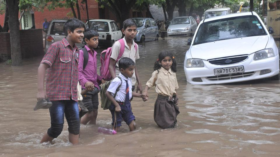 Rains also lashed neighbouring towns including Mohali, Patiala and Fatehgarh Sahib in Punjab, and Panchkula and Ambala in Haryana, MeT department officials said. Students walking waterlogged street in sector 19, Panchkula, on Thursday.  (Sant Arora/HT Photo)