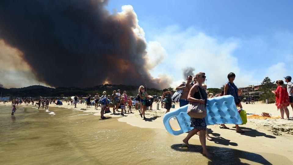 People leave the beach with their belongings as a fire burns a forest behind them in Bormes-les-Mimosas. (Anne-Christine / AFP)