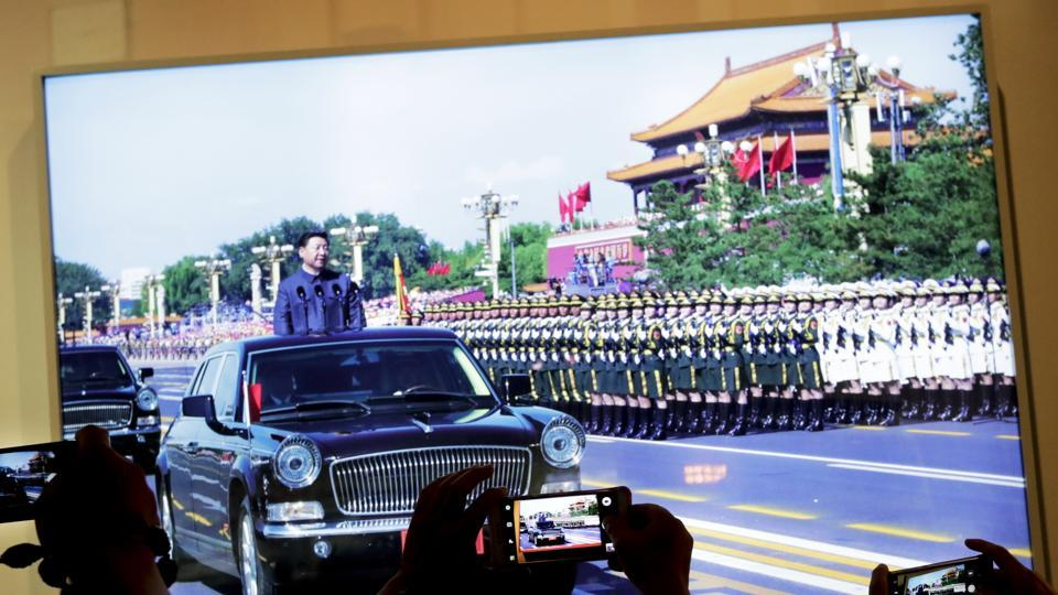 People take smartphone pictures of a display photo showing Chinese President Xi Jinping inspecting the army at the 2015 military parade, at the military museum in Beijing, Thursday.