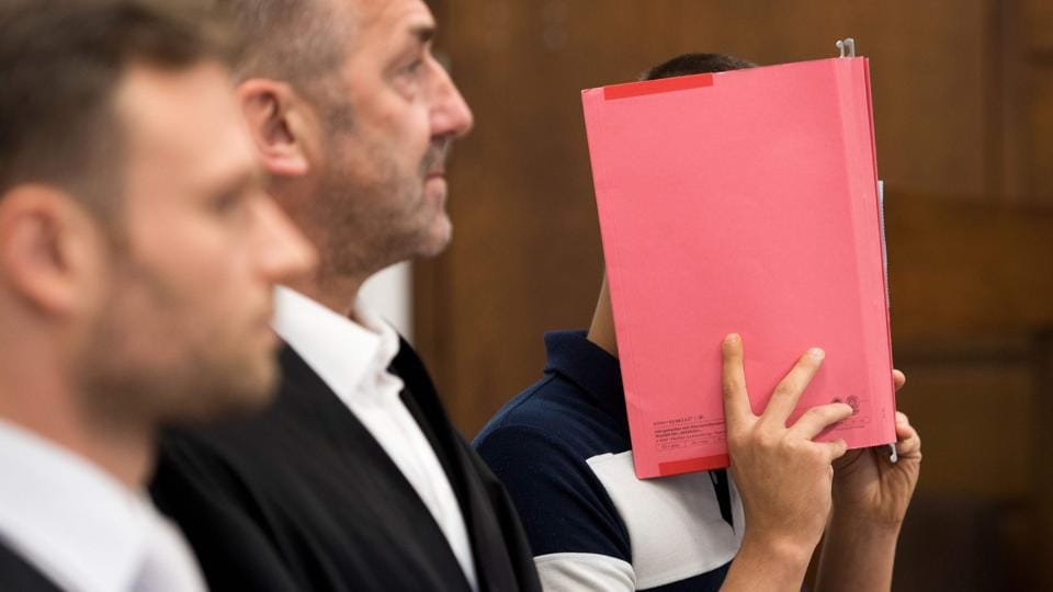 Picture taken on July 21, 2017 shows a 29-years-old defendant hiding his face behind a folder as he stands next to his lawyers at a courtroom in Cologne, western Germany.