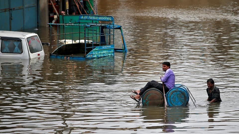 A man uses a makeshift raft to move out of a flooded neighbourhood after heavy rains in Ahmedabad. Approximately 600 people have died in floods and landslides across the country this year. (Amit Dave / REUTERS)