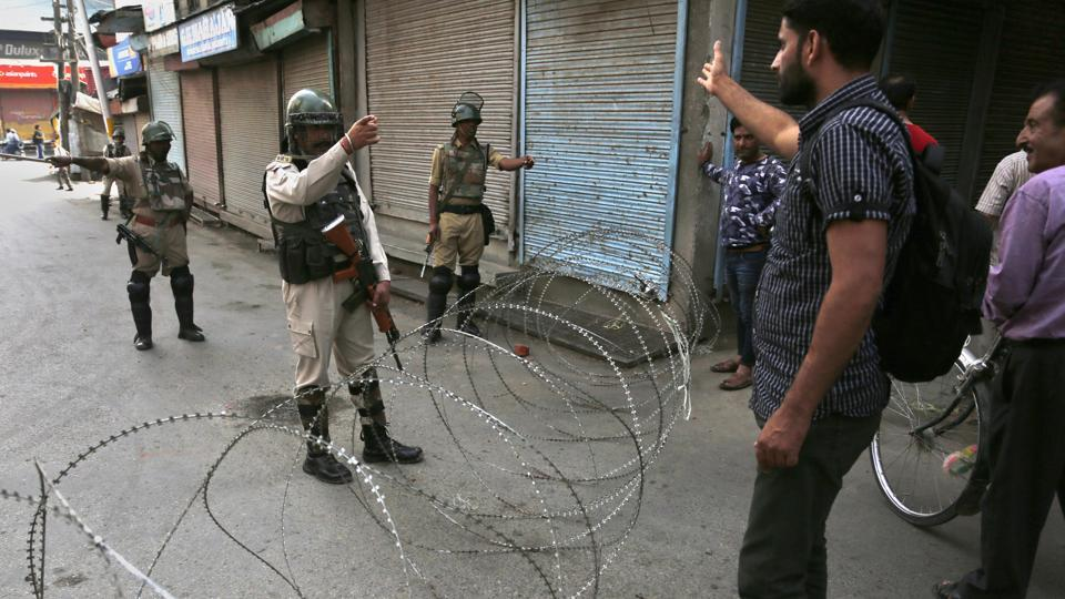 A Kashmiri man argues with a paramilitary soldier at the temporary checkpoint during restrictions in Srinagar on Friday.