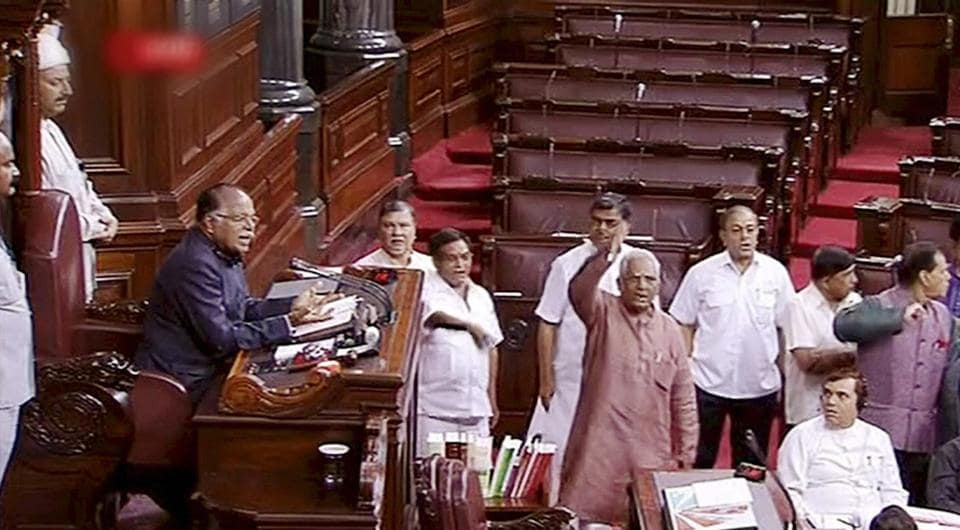 Opposition members protest in the well of Rajya Sabha in New Delhi on Friday.