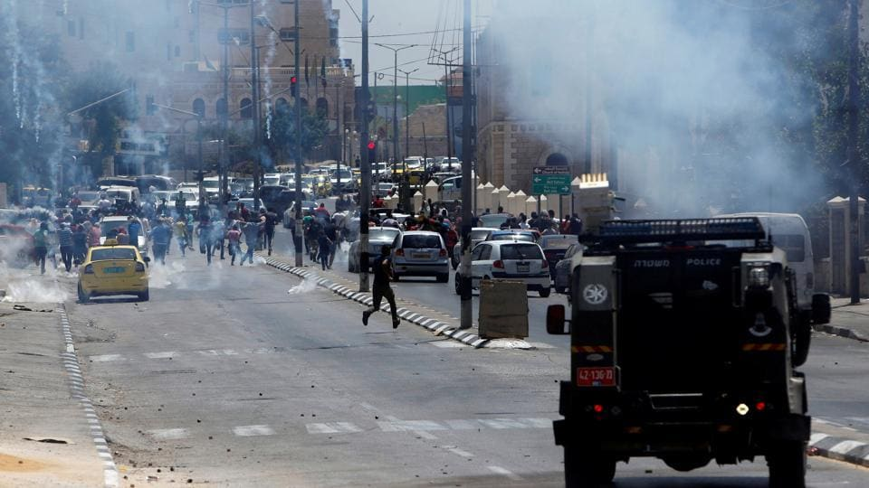Palestinian protesters run for cover from tear gas fired by Israeli troops during clashes in the West Bank city of Bethlehem July 28, 2017.