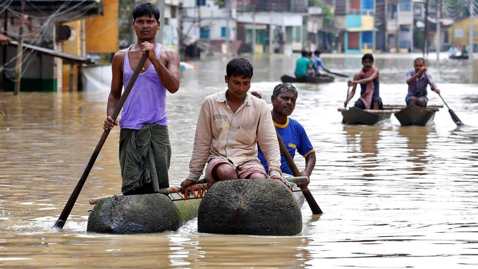 People paddle their boats as they try to move to safer places along a flooded street in West Midnapore district, in the eastern state of West Bengal. (Rupak De Chowdhuri / REUTERS)