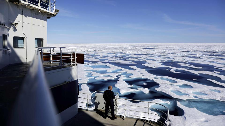 Canadian Coast Guard Capt. Victor Gronmyr looks out over the ice covering the Victoria Strait, visibly pockmarked by signs of melting in the summer months. (David Goldman / AP)