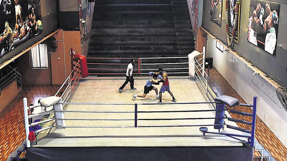Maharashtra's national bronze medallist boxer Akshay Mare (blue) practices with his friend Kishor Gite under the guidance of Rakesh Bhanu, during a training session at Lahuji Vastad Salve Boxing Training Centre at Bhawani Peth. Mare is struggling to make a living as a boxer and delivers papers to make money.