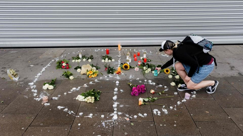 A woman places a candle at a makeshift memorial of flowers and candles arranged like a peace sign on Saturday in Hamburg, Germany, at the site of a knife attack.