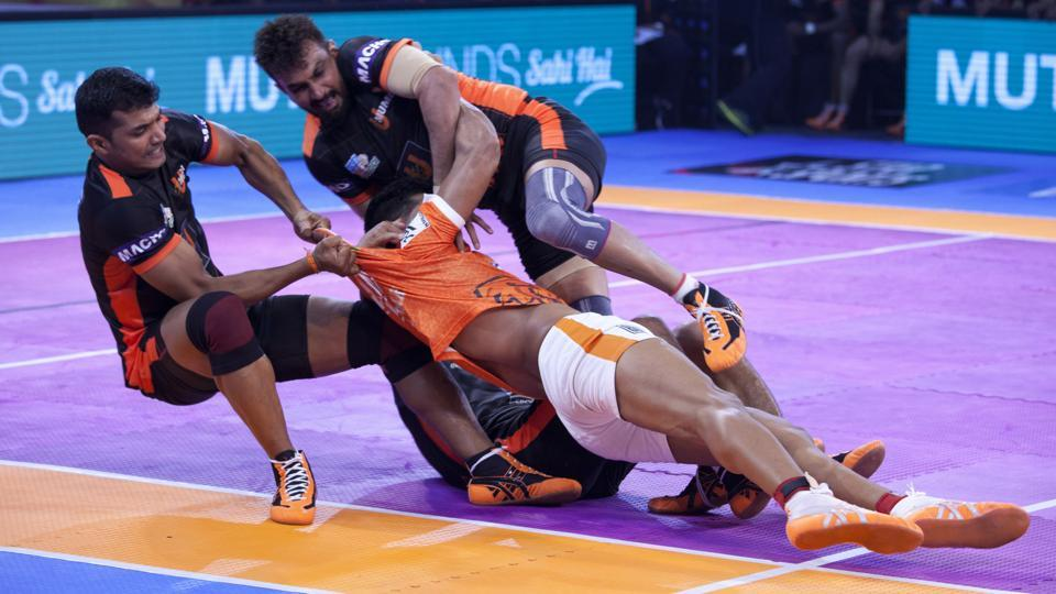 U Mumba players unsuccessfully pin down Puneri Paltan's Deepak Hooda, in orange, during their Pro Kabaddi League match.